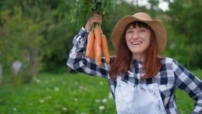 愉快的女性农夫是开掘和拿着从他的庭院剧情收获的红萝卜庄稼  传统生态 股票视频