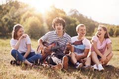 愉快的女性和男学生享受室外的野餐,坐一起编组,在他们自己中笑并且耍笑,唱歌曲到吉他, 库存图片