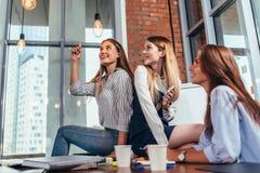 愉快的女性少年坐看和指向时髦的电灯泡和放松在休息期间的桌之间 免版税库存照片