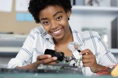 愉快的女性数字电子工程师审查的计算机个人计算机在实验室 免版税库存图片