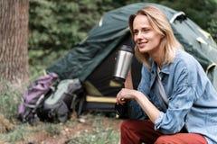愉快的女性旅游享用的饮料在森林里 免版税图库摄影