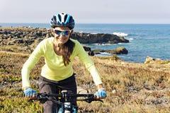 愉快的女性旅游骑自行车者骑马登山车画象  免版税库存照片