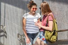 愉快的女性朋友在街道,在地铁附近的立场,互相的份额新闻上一起见面,佩带时髦树荫,举行背包, te 免版税库存图片