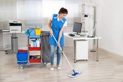 愉快的女性管理员擦的地板在办公室 免版税库存照片