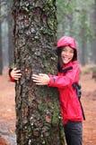 愉快的女性结构树hugger 免版税库存照片