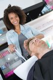 愉快的女性美发师洗涤的男性客户头发 免版税图库摄影