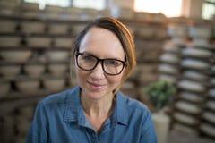 愉快的女性陶瓷工在瓦器商店 免版税库存照片