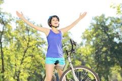 愉快的女性骑自行车的人用在自行车的被举的手户外 免版税库存照片