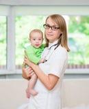 愉快的女性医生儿科医生和患者儿童婴孩 免版税库存照片