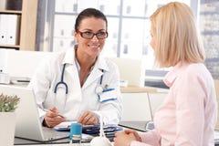 愉快的女性医生在有患者的办公室 免版税库存照片