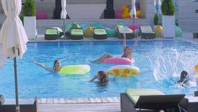 愉快的女朋友公司在游泳池和女朋友放松有此外可膨胀的圆环跃迁的浇灌与 股票录像