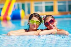 愉快的女朋友喜欢游泳在水池 免版税图库摄影