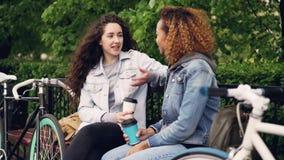 愉快的女朋友是谈话和笑拿着多哥咖啡坐长凳在有自行车的公园 现代 影视素材