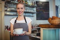 愉快的女服务员服务饮料画象在咖啡馆的 免版税库存图片