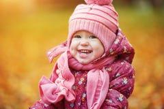 愉快的女婴孩子户外在公园在秋天 免版税库存图片