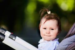 愉快的女婴的画象一辆婴儿推车的在城市公园阳光照耀天 免版税库存照片