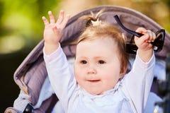 愉快的女婴的画象一辆婴儿推车的在城市公园阳光照耀天 图库摄影