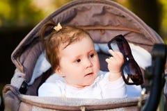 愉快的女婴的画象一辆婴儿推车的在城市公园阳光照耀天 库存图片
