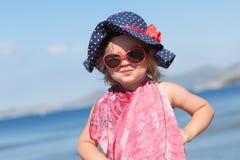 愉快的女婴画象帽子和太阳镜的 免版税库存图片