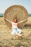 年轻愉快的妇女享受在堆的夏天秸杆前面 免版税库存照片