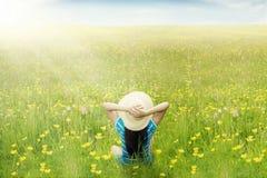 愉快的妇女享受在草甸的春天 免版税库存图片