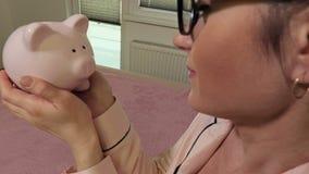 愉快的妇女亲吻的桃红色存钱罐 股票录像
