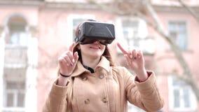 年轻愉快的妇女佩带的网际空间虚拟现实耳机玻璃获得乐趣外面在街道上在灰棕色穿破外套 影视素材