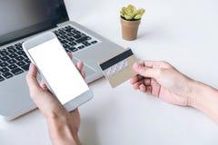 愉快的妇女使用巧妙的电话的和信用卡登记付款 免版税库存照片