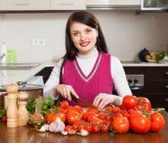 愉快的妇女切口蕃茄 免版税库存图片