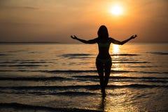 愉快的妇女剪影比基尼泳装的在日落的海滩 库存照片