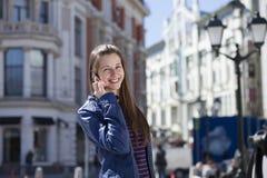 年轻愉快的妇女叫由在街道上的电话 免版税库存图片