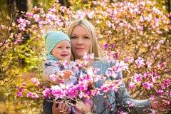 愉快的妇女和女婴在开花的春天森林里用迷迭香 免版税库存照片