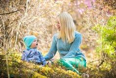 愉快的妇女和女婴在开花的春天森林里用迷迭香 库存照片