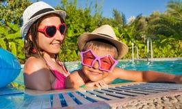 愉快的妇女和她的儿子佩带的太阳镜在水池 库存图片