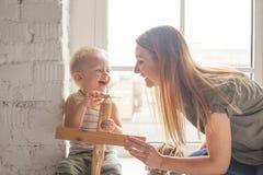 愉快的妇女和她逗人喜爱的矮小的儿子微笑着 图库摄影