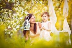 愉快的妇女和孩子在开花的春天从事园艺。儿童kissi 免版税库存图片