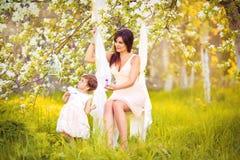 愉快的妇女和孩子在开花的春天从事园艺。母亲节 免版税库存照片