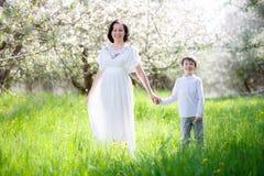 愉快的妇女和孩子在春天庭院里 免版税库存图片