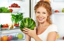 愉快的妇女和开放冰箱用水果,蔬菜和他 免版税库存照片