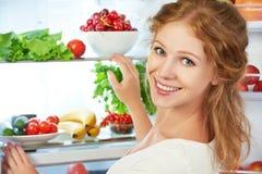 愉快的妇女和开放冰箱用水果,蔬菜和他 免版税图库摄影