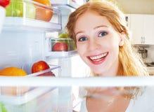愉快的妇女和开放冰箱用水果,蔬菜和他 免版税库存图片