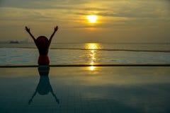 愉快的妇女和放松,坐由游泳池 库存照片