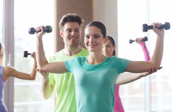 愉快的妇女和教练员与哑铃在健身房 库存图片