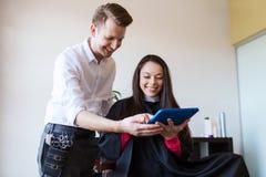 愉快的妇女和美发师有片剂个人计算机的在沙龙 库存图片