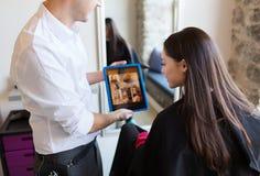 愉快的妇女和美发师有片剂个人计算机的在沙龙 免版税库存图片