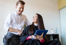 愉快的妇女和美发师有片剂个人计算机的在沙龙 图库摄影