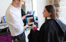 愉快的妇女和美发师有片剂个人计算机的在沙龙 免版税库存照片