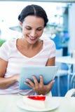 愉快的妇女喜欢使用她的片剂 免版税库存照片