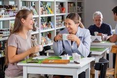 愉快的妇女喝咖啡在超级市场 免版税库存照片
