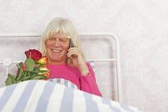 愉快的妇女在与玫瑰和电话的床上 免版税库存图片
